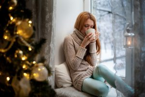 woman sipping hot drink in the wintertime, indoors