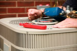 technicians-hands-with-tools-on-top-of-outdoor-ac-unit